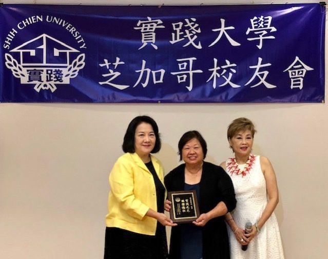 芝加哥實踐大學校友會新任會長郭笑榮(左)在會中頒贈刻著「實踐之光、服務僑社」的感謝牌給陳美麗(中)
