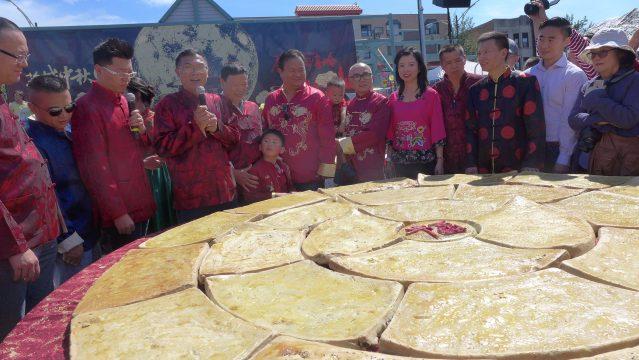 照片二:福建總商會會長鄭時坦向大家介紹千人大月餅