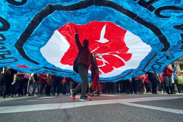 A child walks under a banner as hundreds of teachers and supporters march in Chicago