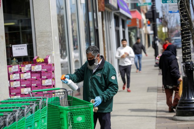 A worker for Patel Brothers grocery store spays and wipes down a shopping cart during the global outbreak of coronavirus disease (COVID-19) in Chicago