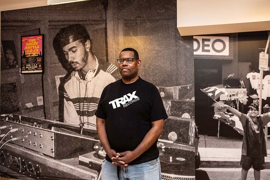 """Marcus """"Mixx"""" Shannon at the Cultural Center, in front of a photo of house pioneer Ron Hardy at the Muzic Box"""