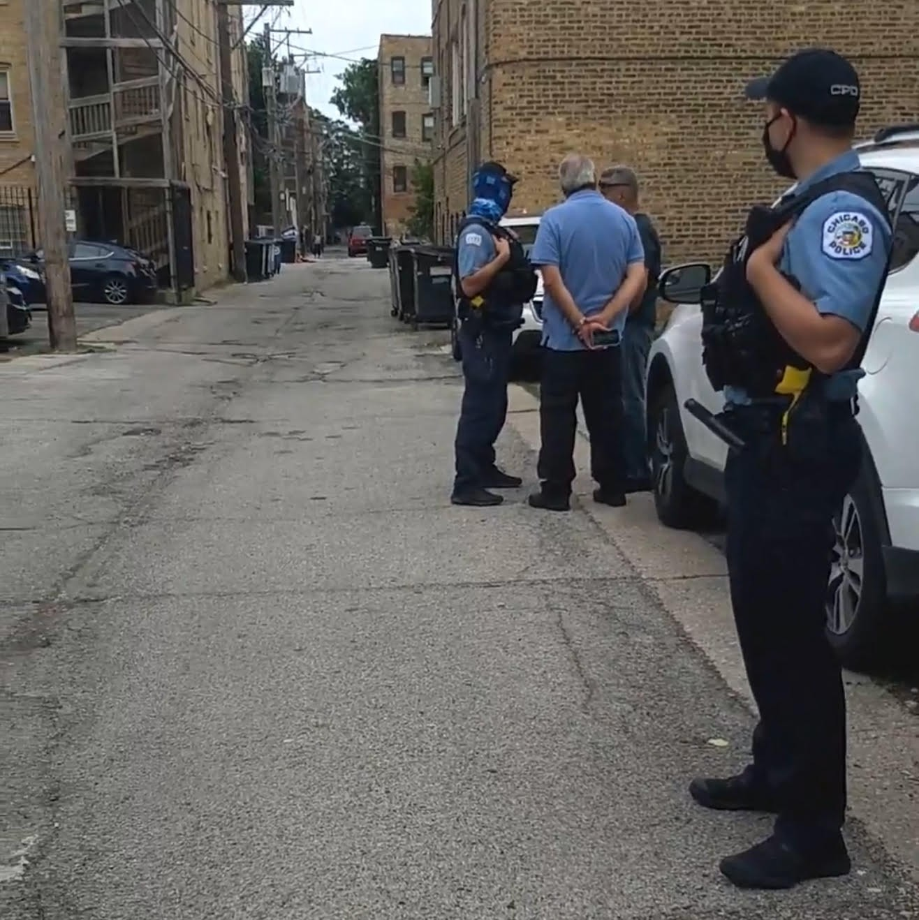 CPD officer Joshua Surgal (with the blue neckwarmer on his face) spoke with the men who extracted a tenant at gunpoint out of earshot of bystanders.