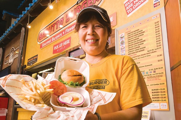 Employee with a Gabutto burger and fries