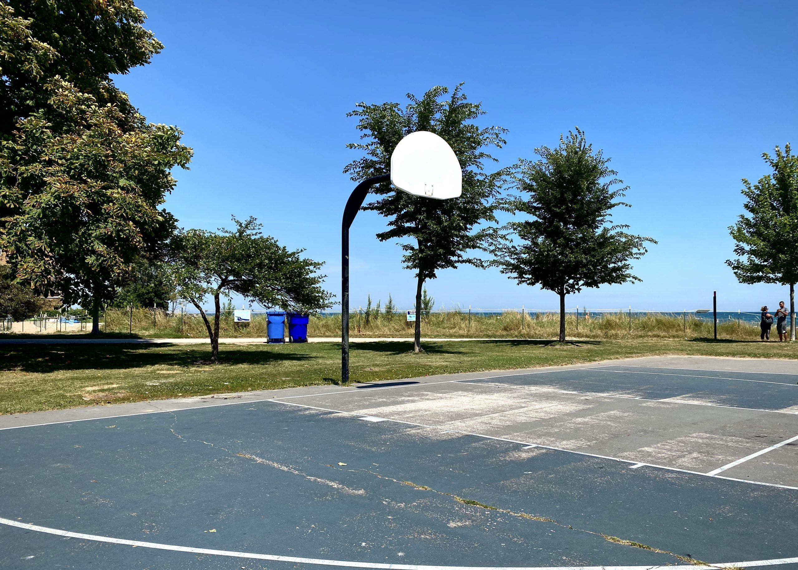 The Loyola Park basketball court in Rogers Park without rims in August 2018. Loyola Park does not feature on the Chicago Park District's list of inactive courts, and it is unclear why the rims here have not been restored here since Chicago resumed park access in its  phased reopening.