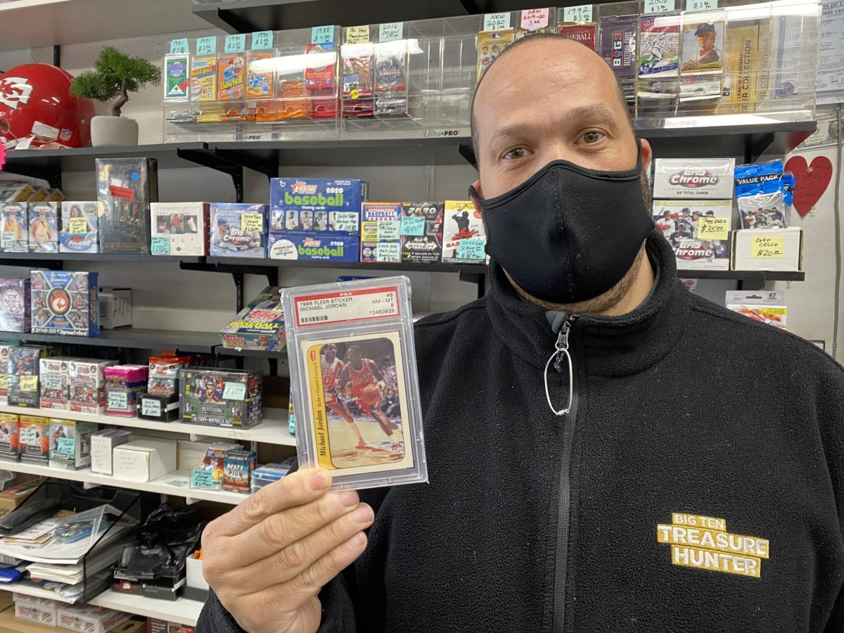 Ronnie Holloway of Elite Sports Cards & comics holds a jewel from his collection, a graded, near-mint 1986 Fleer rookie sticker of Chicago Bulls legend Michael Jordan. The card is worth around $10,000.