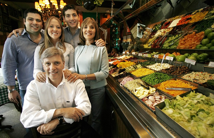 Richard Melman (front) poses by the salad bar in his first reataurant, R.J. Grunt's, in Chicago's Lincoln Park neighborhood with his family.