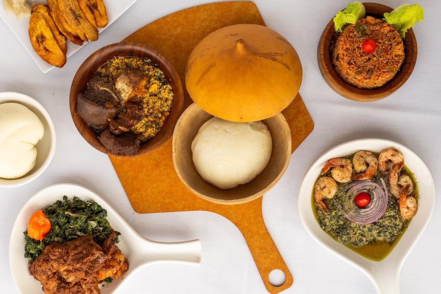 Pounded yam <em>fufu</em> and <em>egusi</em> (center) with goat and fish; around the center clockwise: corn <em>fufu</em>, plantain and <em>bobolo</em>, jollof rice, crevette, and <em>khati khati</em>