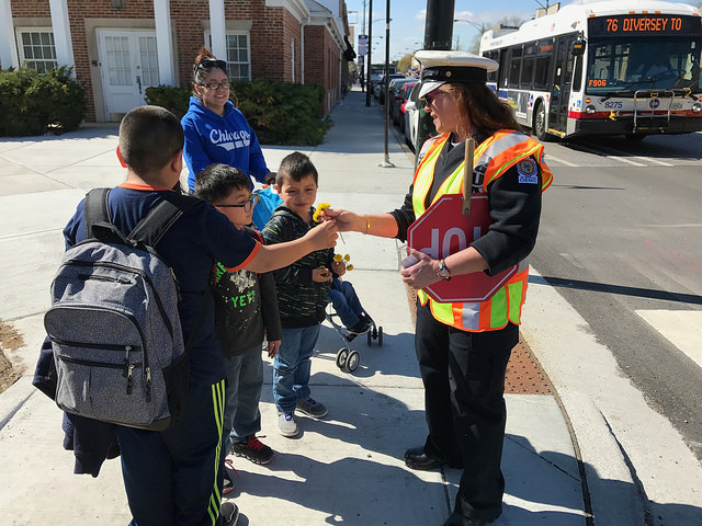 Ana the crossing guard gets dandelions from Murphy Elementary students.