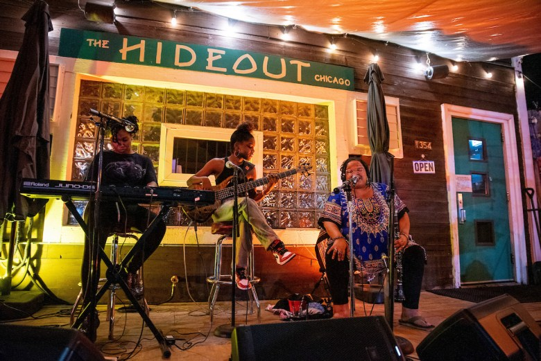 The Sistazz of the Nitty Gritty—pianist-vocalist Anaiet, bassist Brooklyn Skye Scott, and multi-instrumentalist Angel Bat Dawid—perform on the Hideout patio in July.