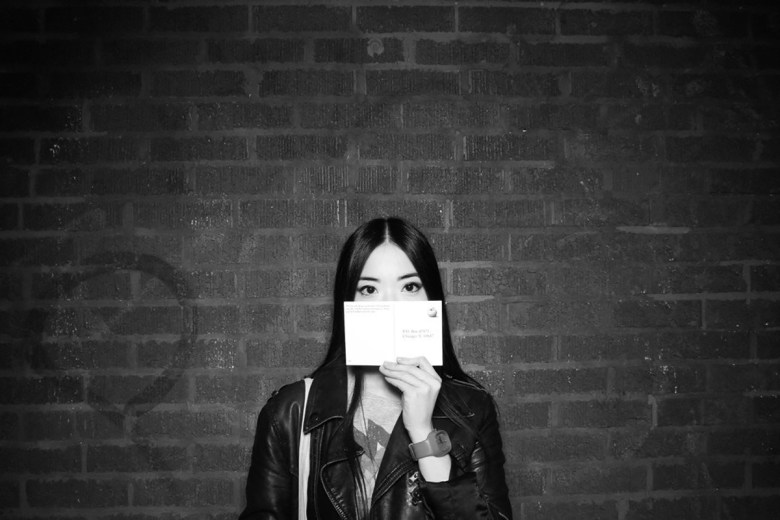 Jenny Lam posing with a postcard in front of a brick wall