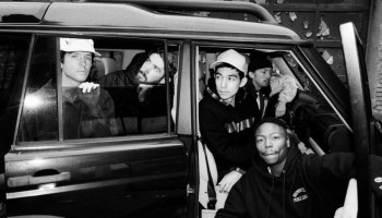 The band Turnstile pose for a photo while sitting in and around a car.