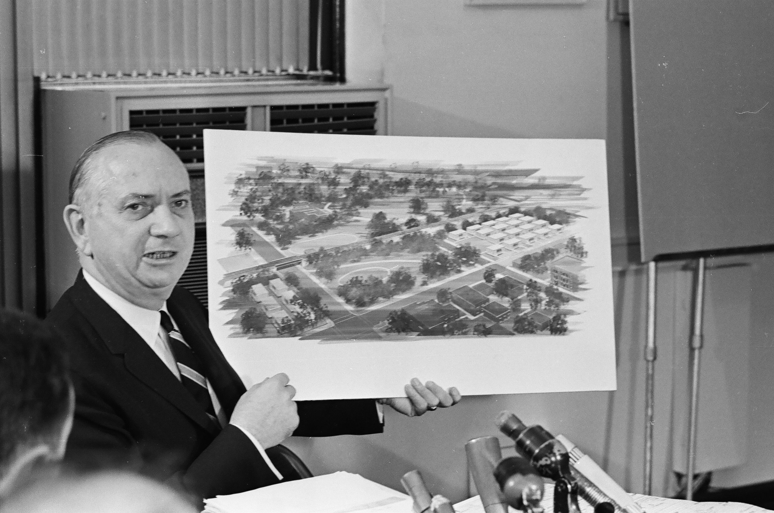 Chicago schools superintendent Benjamin C. Willis holds a watercolor rendering of the planned campus of portable classrooms.