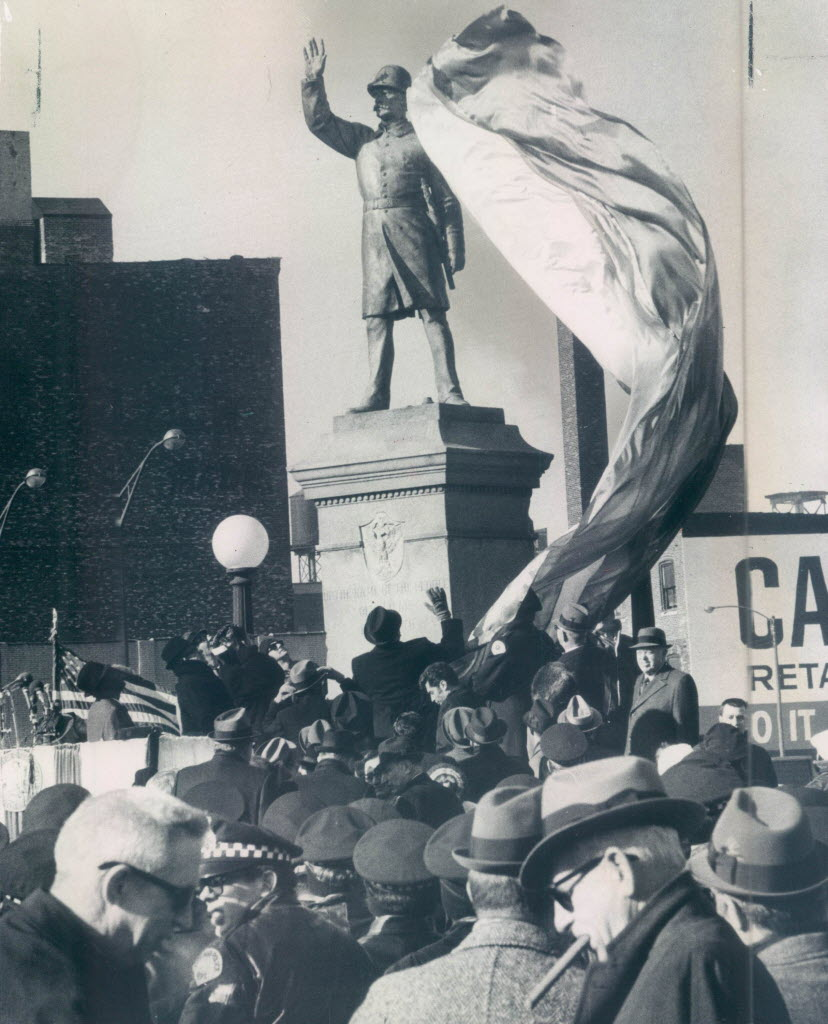 The police officer statue in Haymarket Square at its rededication in 1971 after it was bombed for a second time. Mayor Richard J. Daley stands in front, saluting.