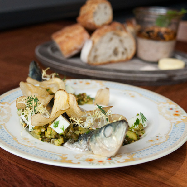 Pickled sardine—a delicious two-headed monster—with a jar of duck confit in the background