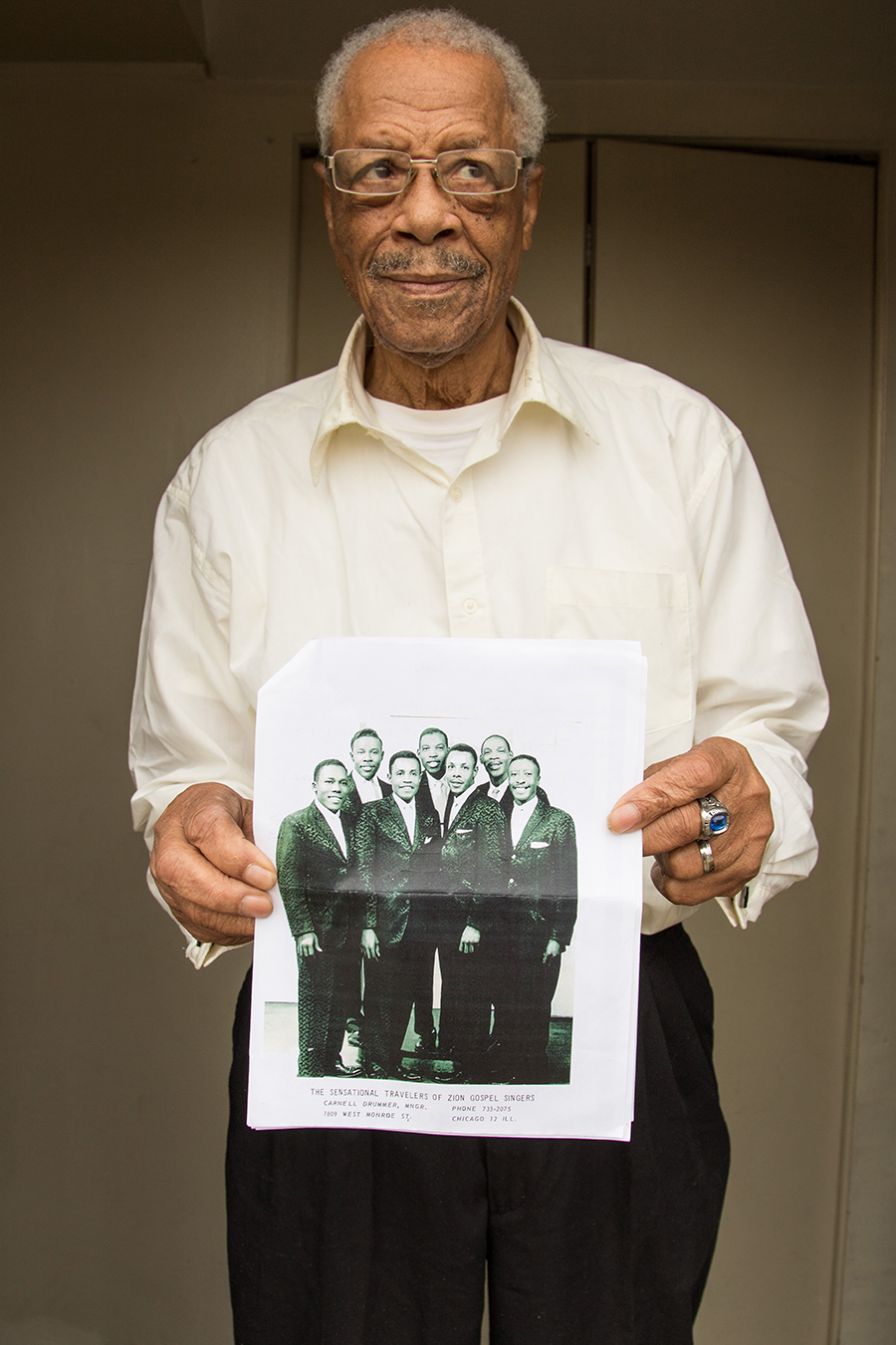 Carnell Drummer holds an old photo of his group the Sensational Travelers of Zion, who have a song on <i>No Other Love</i>. Drummer is second from right in the front row.