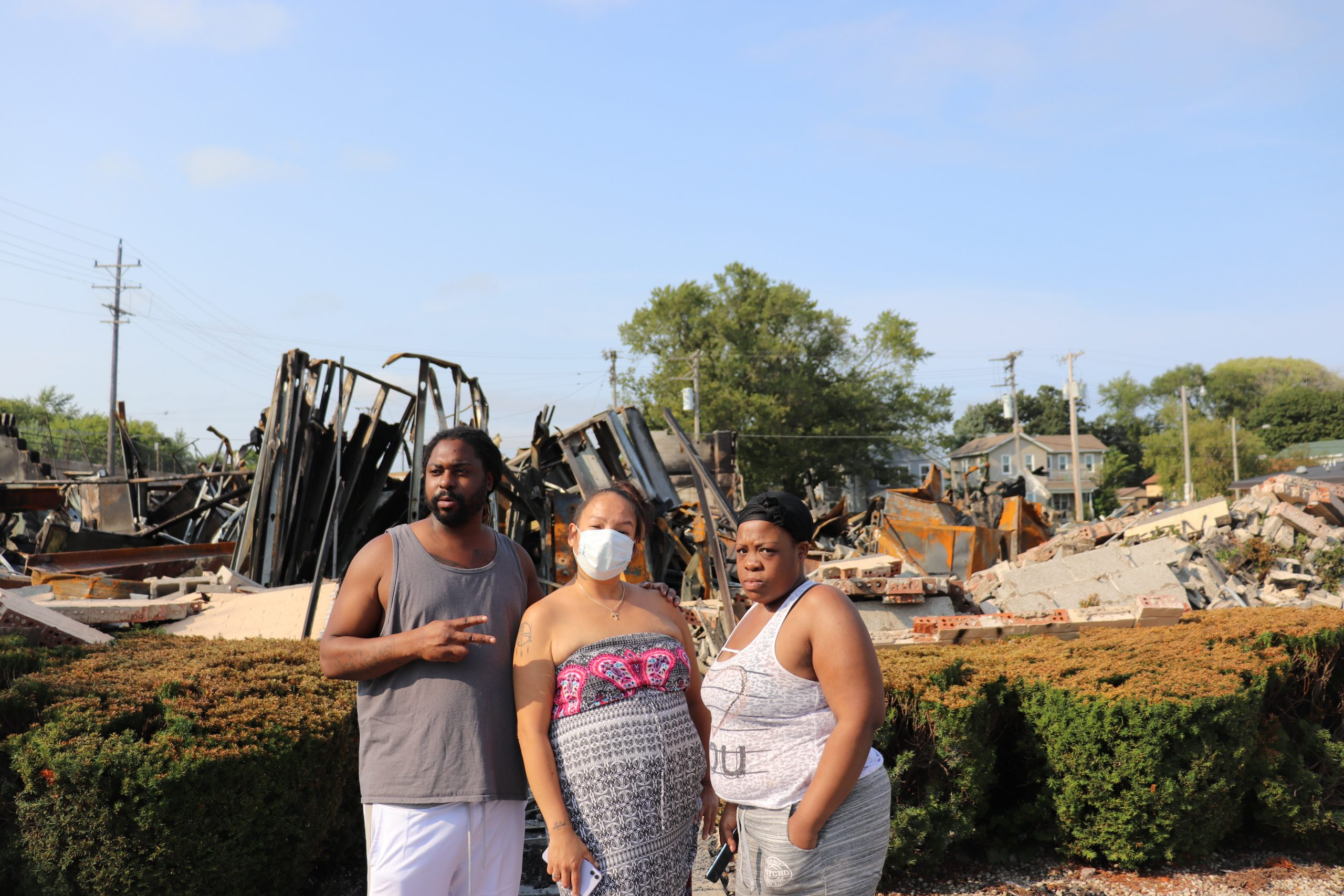 Trurun Clary stands in front of rubble of the former Department of Corrections building with Tre Daniels (middle) and Brittany Collins (right) on Tuesday, August 25,2020.