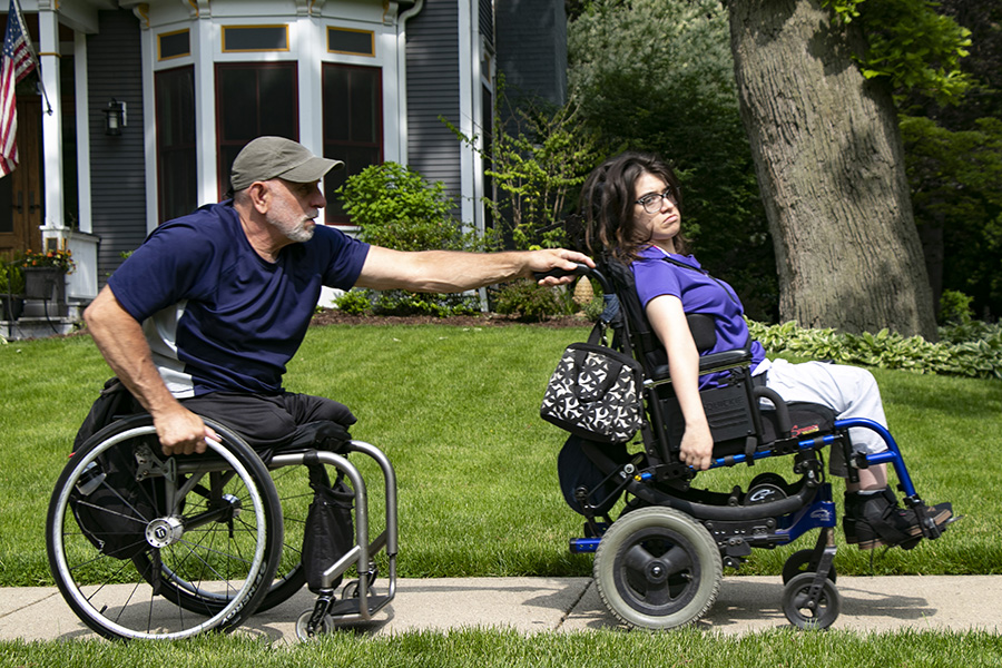 Lenzo wheels with Cynthia outside their house in Oak Park. Cynthia's cerebral palsy makes it difficult for her to move and maintain balance.