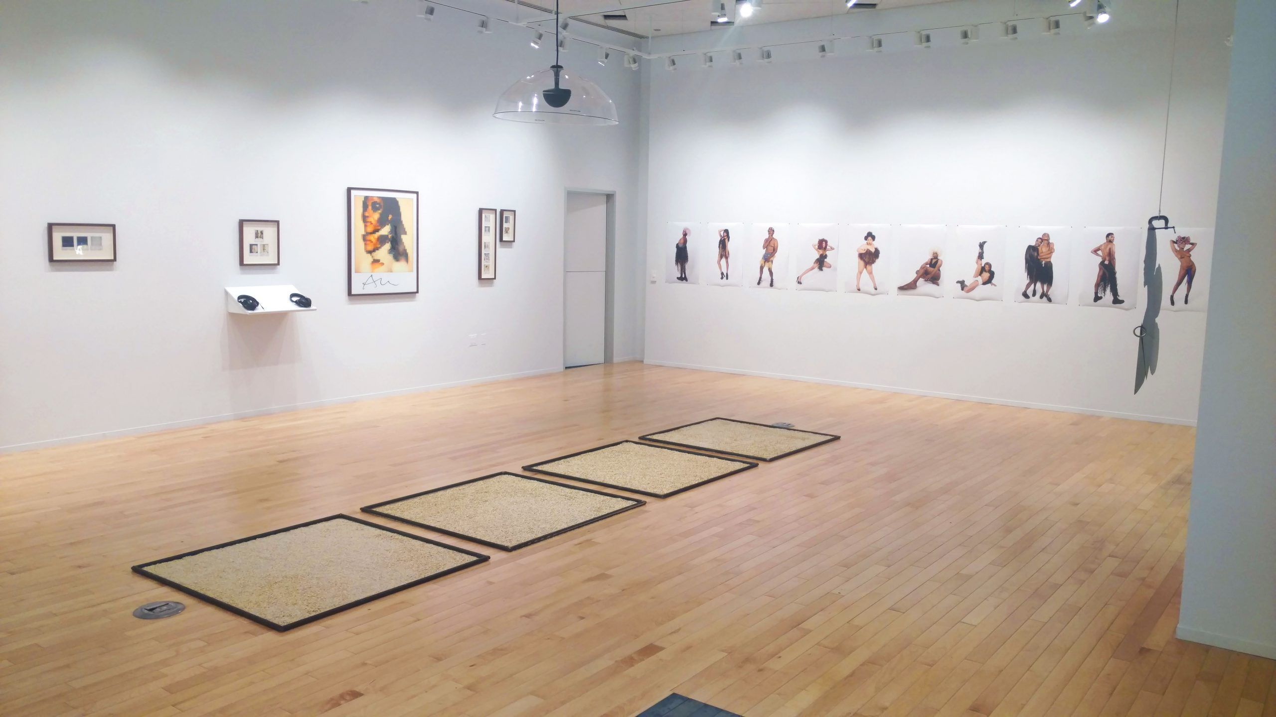 """""""De Nue"""" in the gallery. <i>Smooth Operator</i> is on the left wall, <i>Black Pinup Project</i> is on the right, and components of <i>Untitled</i> are in the center."""