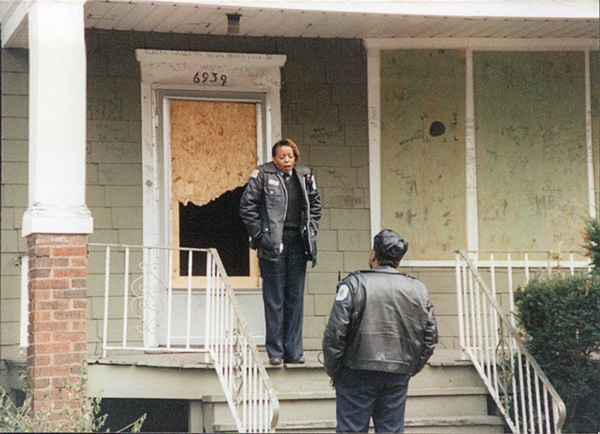 Officer Adams, standing on a porch in the early 2000s