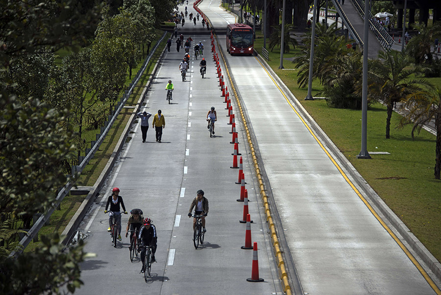 Riders and pedestrians enjoy Bogotá's weekly Ciclovía on streets temporarily closed to motor vehicles.