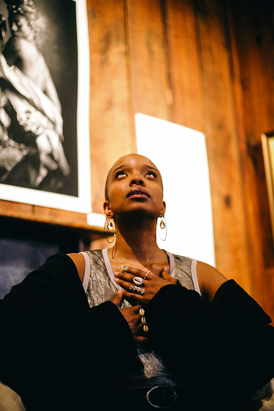 """Jamila Woods at the SSCAC exhibit """"Flowers in the Garden."""" The photo at upper left is a 2019 print titled <i>Worldly Roxi</i> by Chicago-based multimedia artist, educator, gallery owner, documentary filmmaker, and musician Tony Smith."""