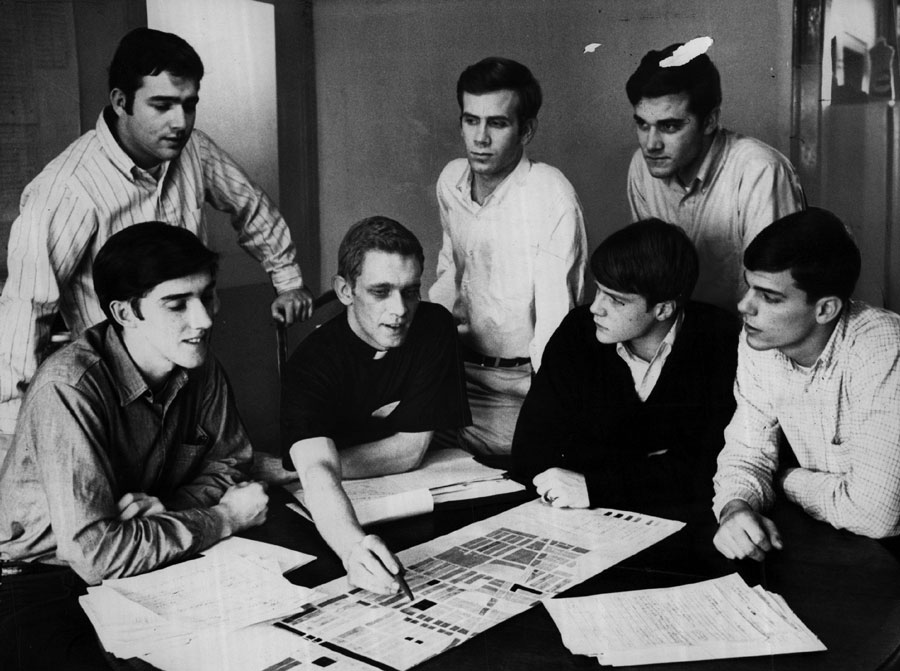 """Jesuit seminarian John R. """"Jack"""" Macnamara huddles with college students helping him combat inflated property contracts in North Lawndale in May 1968."""