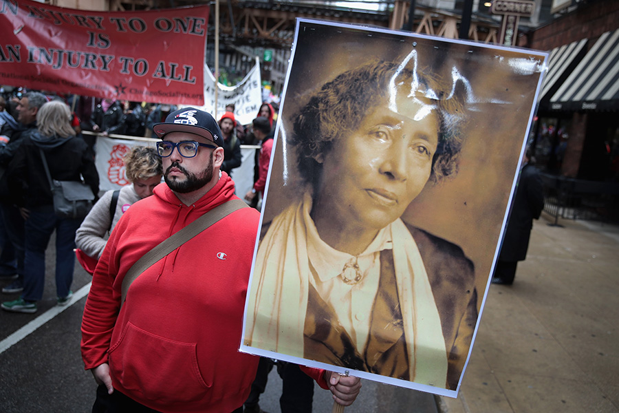 A demonstrator at a downtown Chicago march on May 1, 2017, celebrates May Day (also known as International Workers' Day) by carrying a portrait of IWW cofounder Lucy Parsons.
