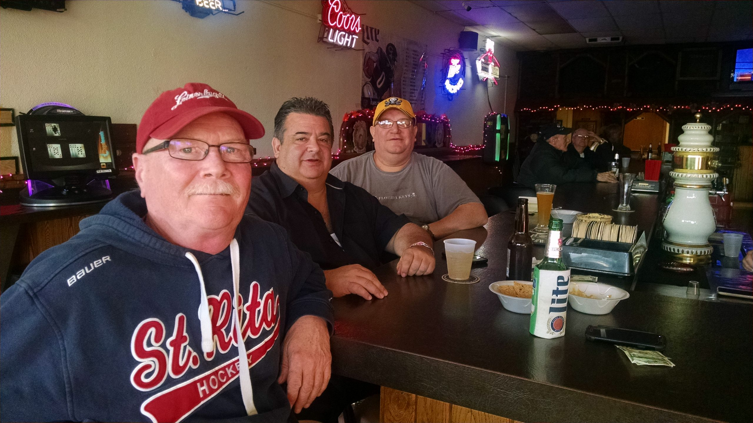 """Ray, Joe, and Drew gather at the """"asshole corner"""" at Buddies, the bar attached to Miska's Liquors in Clearing."""