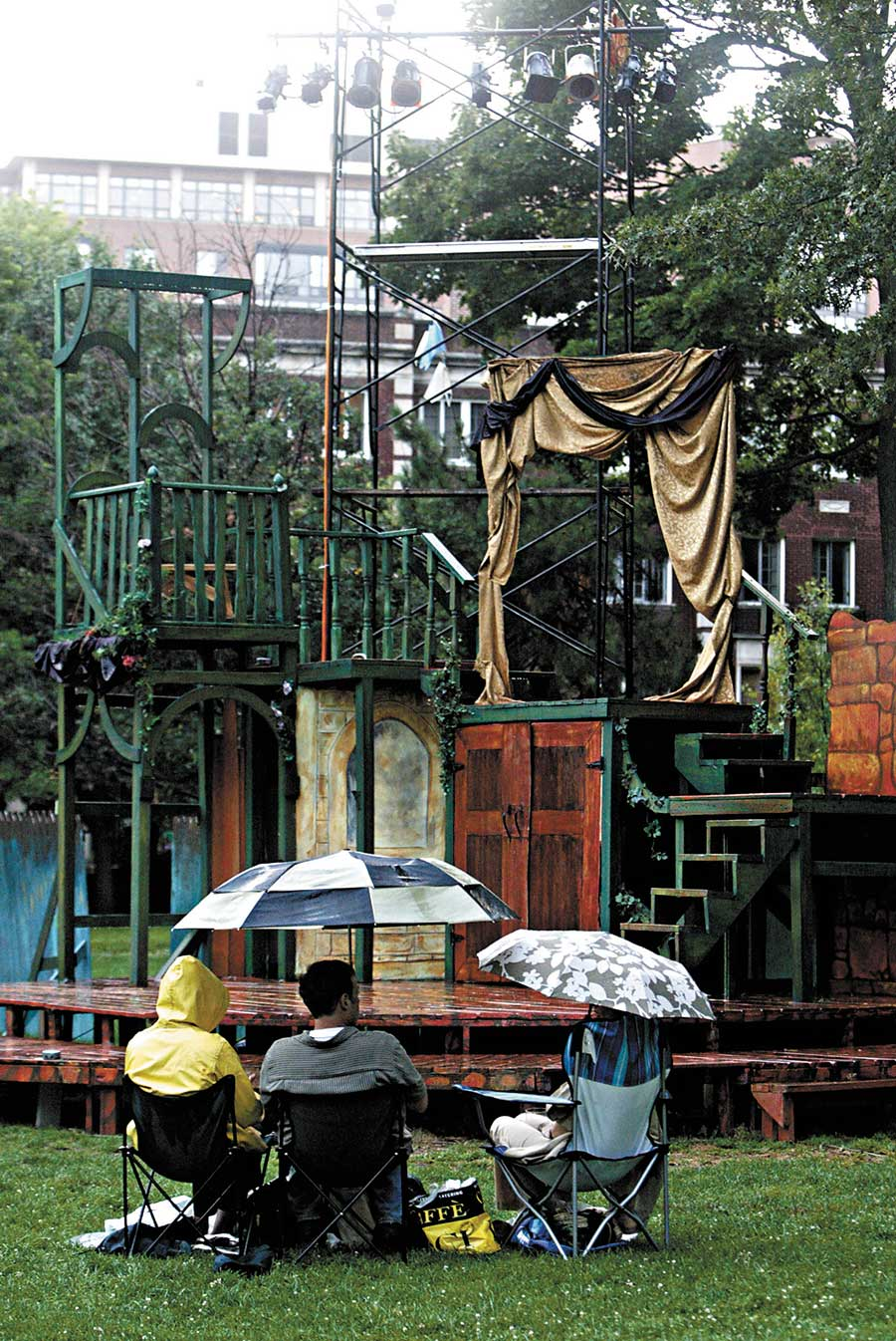 Theatre-goers wait for the rain to stop before the Oak Park Festival Theatre's 2009 production of <i>Cyrano de Bergerac</i>.