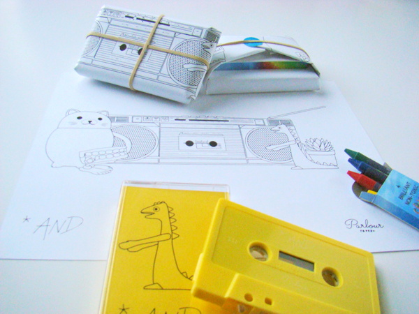 The compilation <i>*And</i>, with the boom-box drawing it comes wrapped in and the crayons it's packaged with