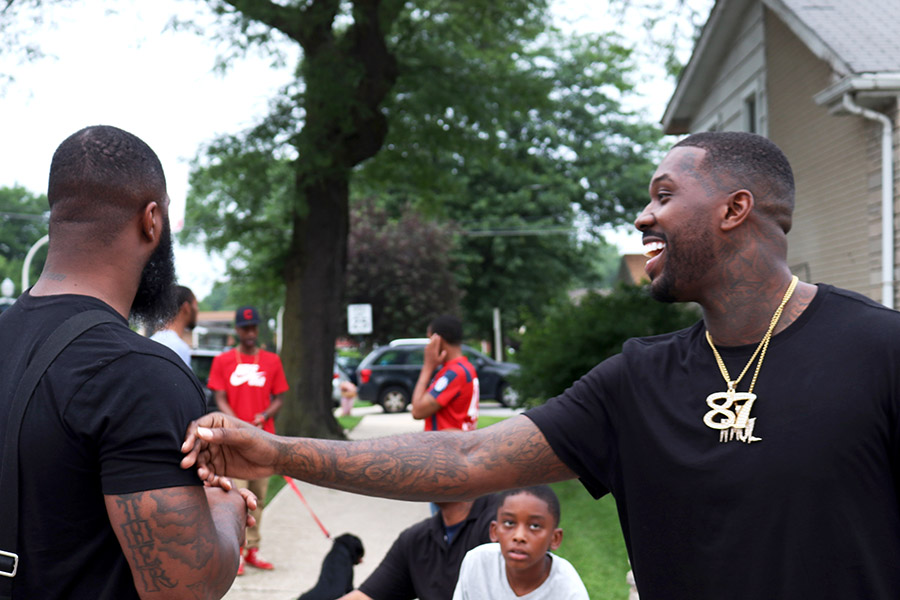 Phor (right) and his brother Don reminisce with friends on the block.