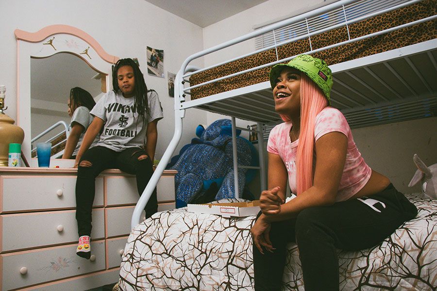 Queen Key on the bottom bunk in her cousins' bedroom in Blue Island, where she used to write her songs. Her 15-year-old cousin Aniya is to the left.