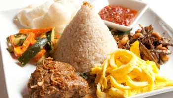 An order of <i>nasi lemak</i>: coconut-milk-saturated rice surrounded by beef <i>rendang</i>, pickled carrot, shredded omelet, fried anchovy, shrimp crackers, peanuts, and spicy sambal