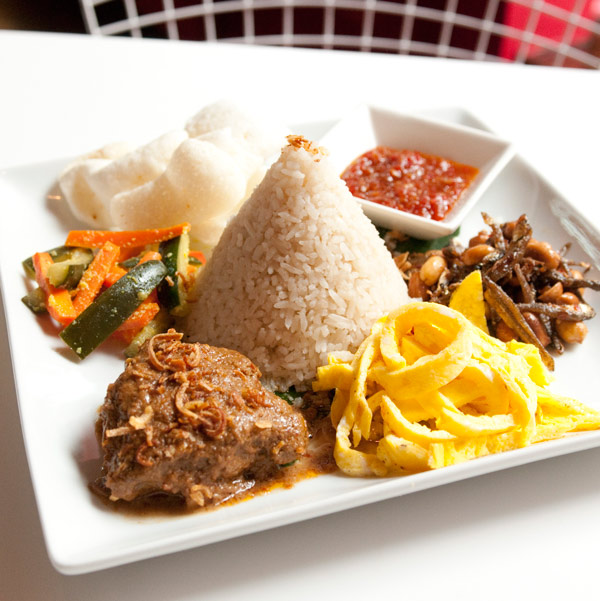 An order of nasi lemak: coconut-milk-saturated rice surrounded by beef rendang, pickled carrot, shredded omelet, fried anchovy, shrimp crackers, peanuts, and spicy sambal