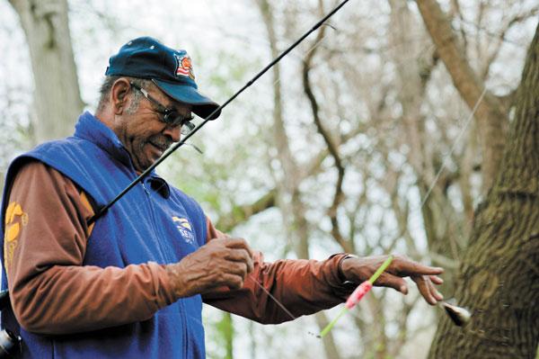 Sterling Bledsoe checks his reel at Jackson Park lagoon.