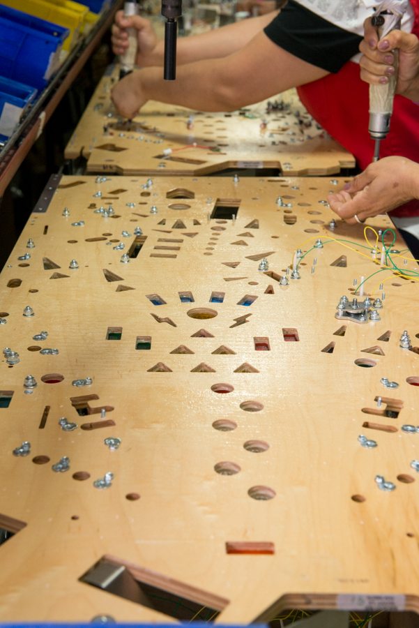 Workers install electronics on the backside of a pinball playfield