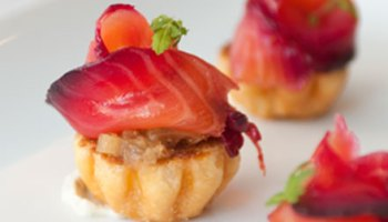 A canape of cured salmon on smudges of sweet fennel jam atop brioche circles