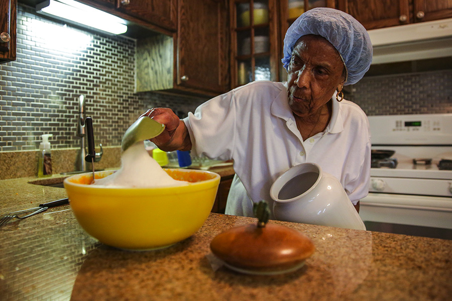 """Mama Lou is famous in the church community not just for her talent as a music director but also for her sweet potato pie. """"I don't measure,"""" she says, scooping sugar in her kitchen."""
