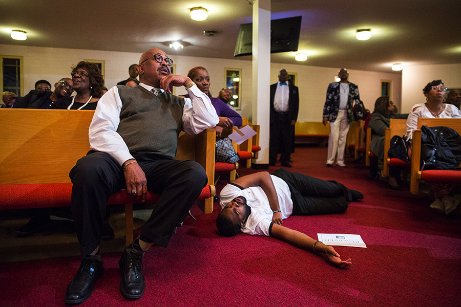 A congregant lies on the floor after feeling the spirit during a Mama Lou choir performance at Greater New Mount Moriah Missionary Baptist Church in Detroit.