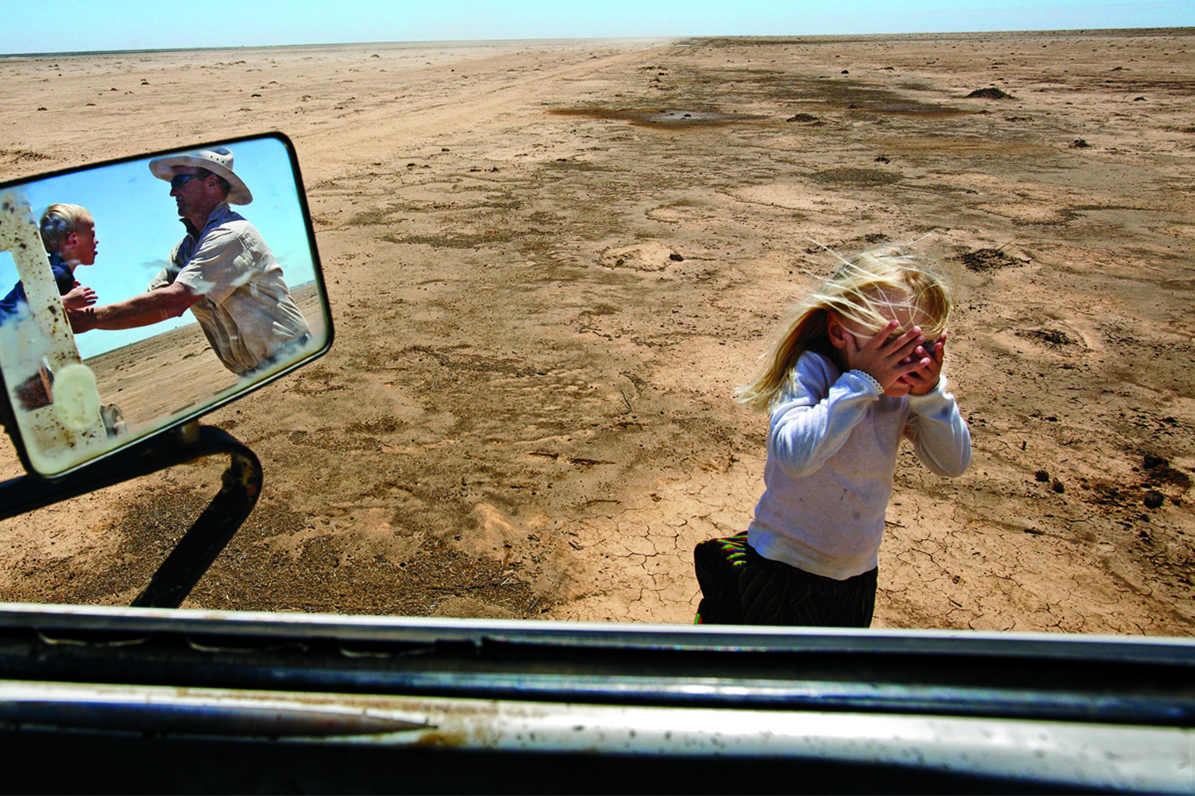 A farmer and his children play in a water-starved field in Australia where his livestock once grazed.