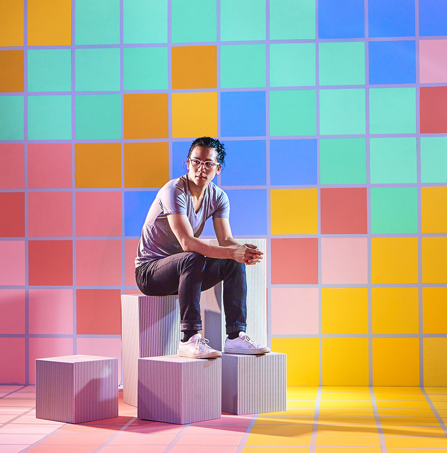 Video game designer William Chyr in a colorful, pixelated landscape