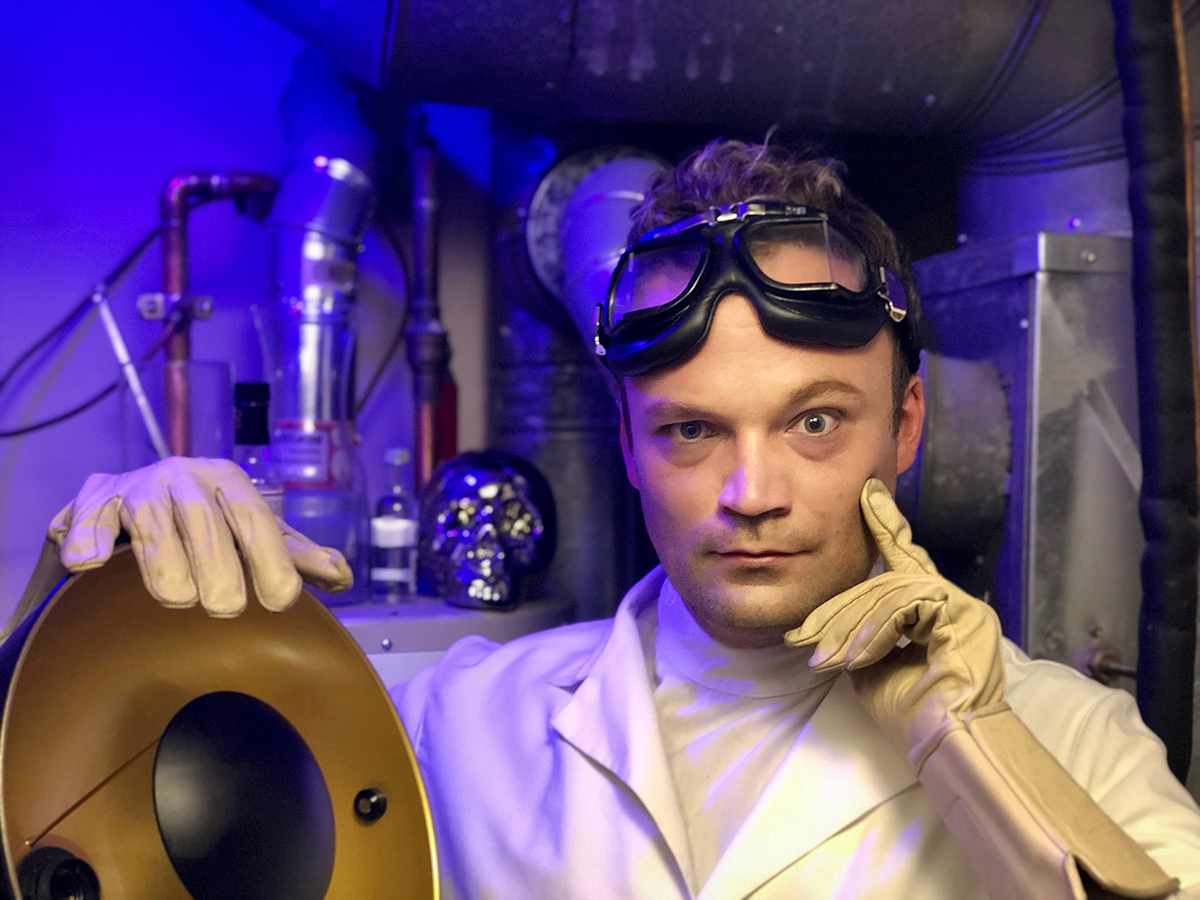 Man in white coat and lab goggles stands in front of lab equipment