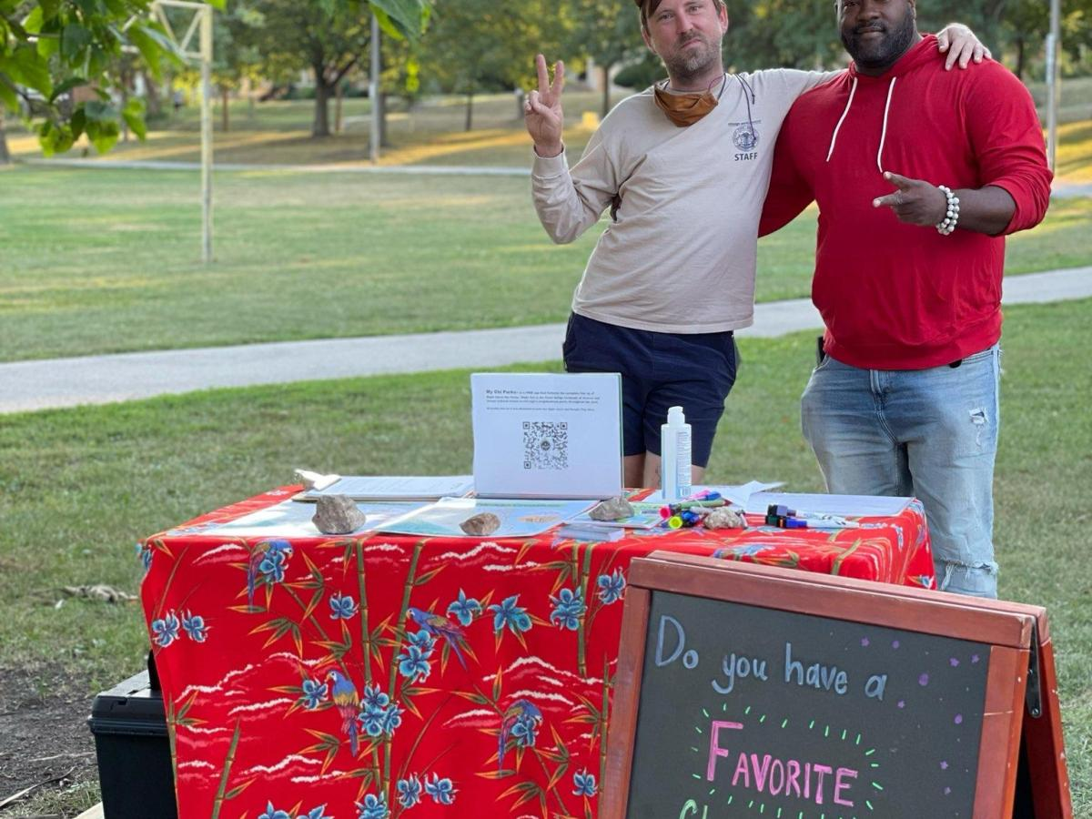 """Two men standing behind a table in a park with a sandwich board reading """"Do you have a favorite Chicago-based musical memory? Tell us about them!"""""""