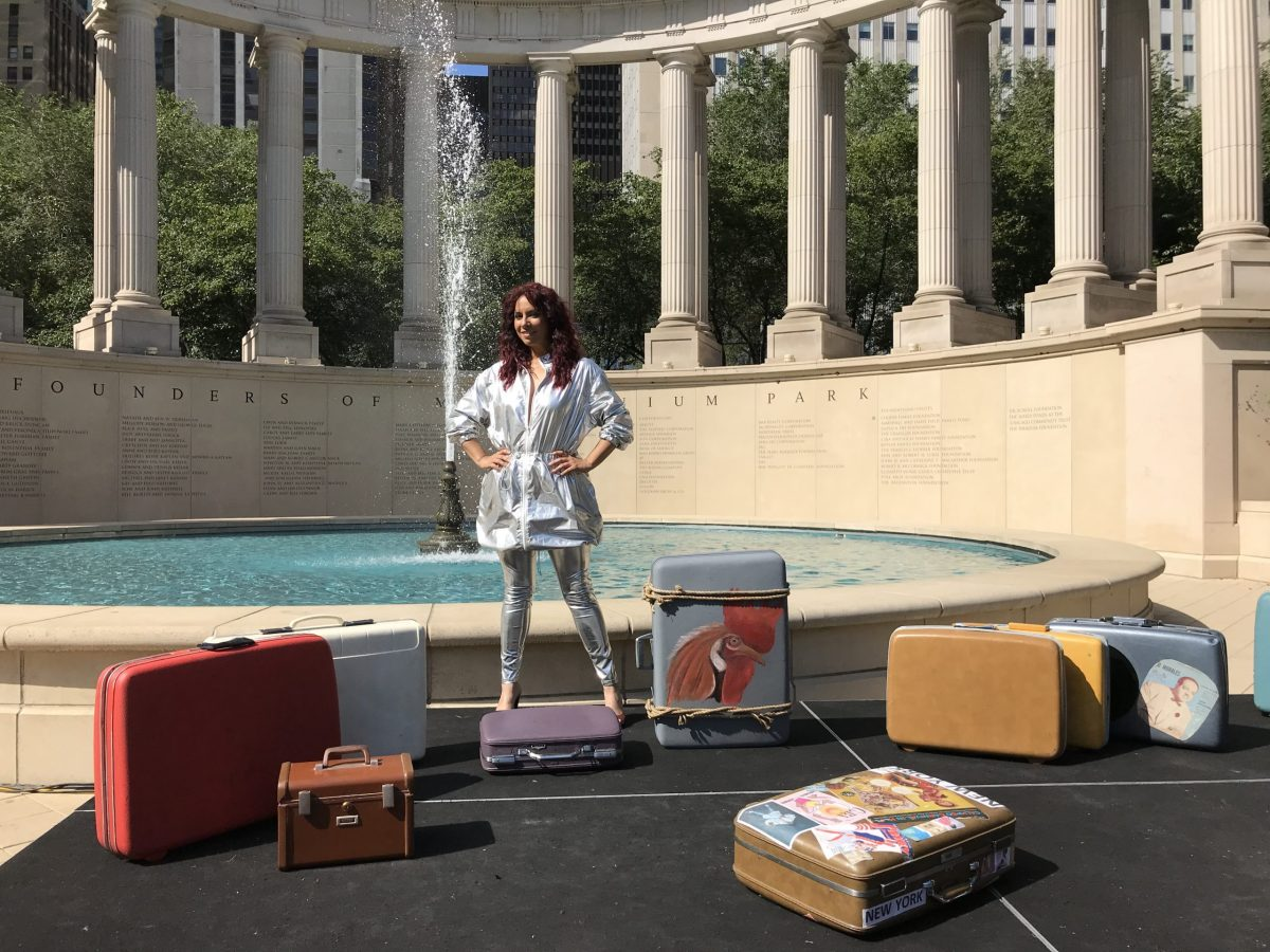 Woman stands in front of columns and fountain in Millennium Park, surrounded by suitcases