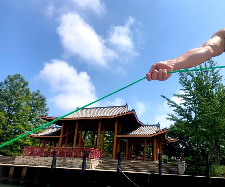 A fisherman holds his casting rope as he floats in the water near Ping Tom Park in Chinatown.