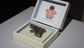 Image of a gun in a toy box with painting of baby in the inside lid
