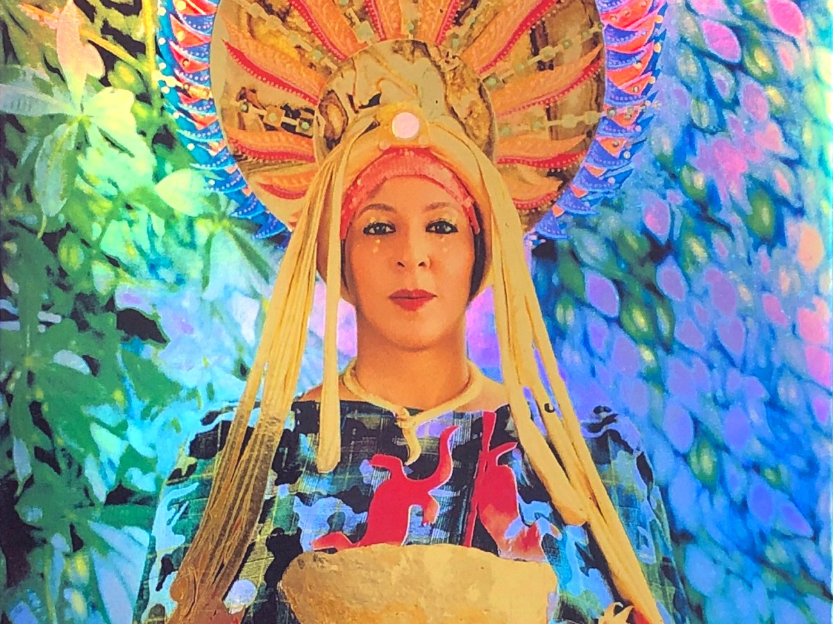 A woman holding a bowl and wearing robes and a headcovering, lots of color behind her (video still from Duyst-Akpem work)