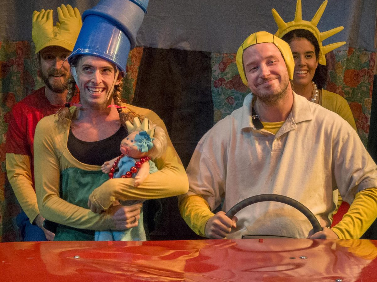 Actors dressed in costumes representing the Simpsons, seated in a red car