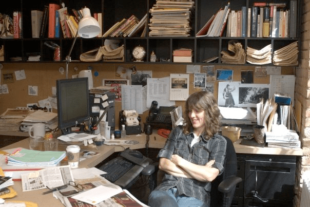 Alison True sitting at desk surrounded by books and paper