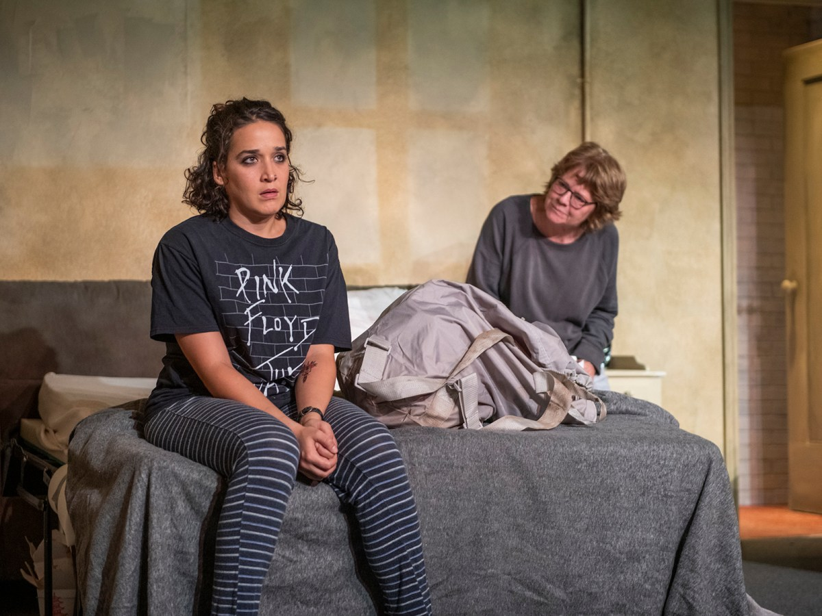 A young woman and an older woman sit on a bed in a dingy room.